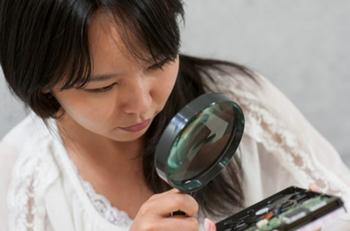 細かい物を拡大鏡でみている女性
