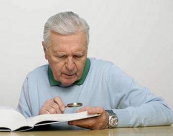 老人が虫眼鏡で本を読んでいるところ